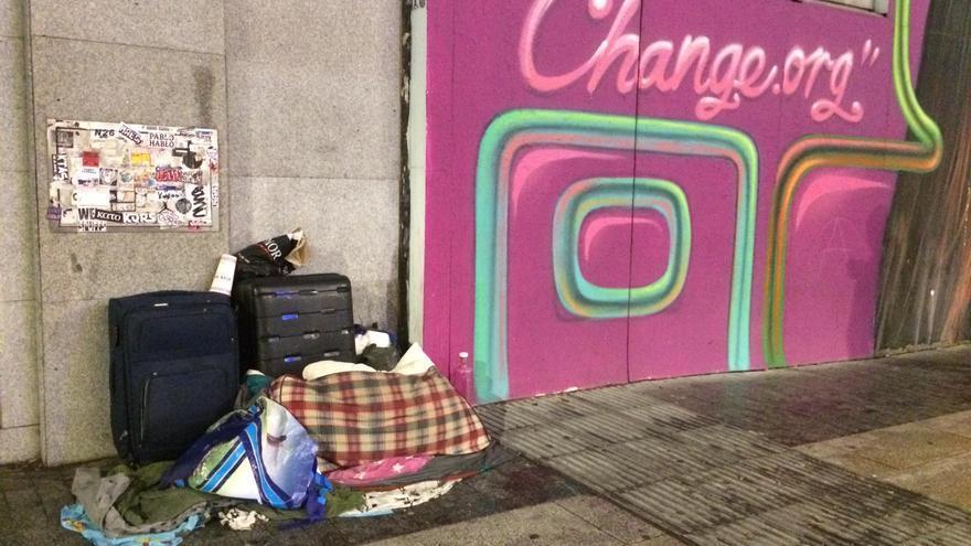 Un montón de mantas y maletas sin dueño aparente al lado de un mural de Gran Vía.