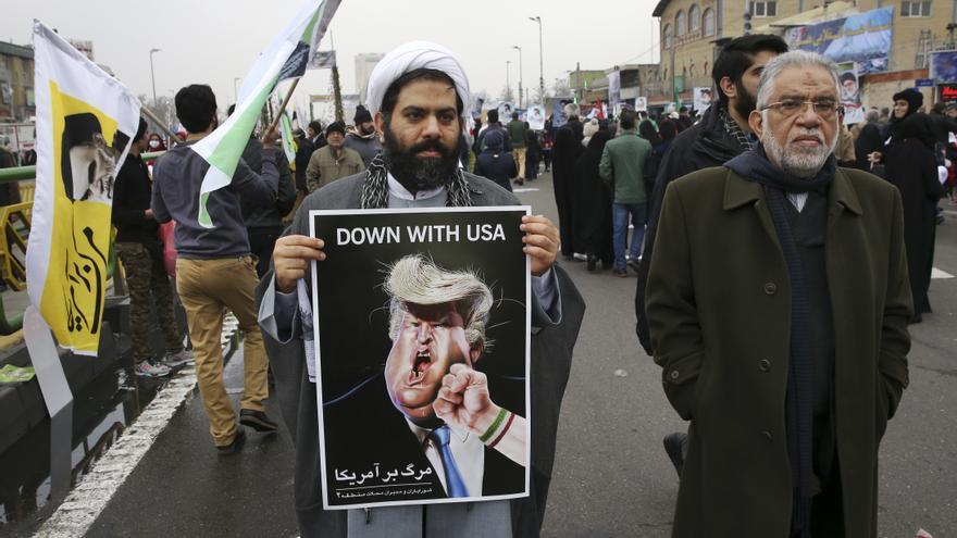 Un iraní celebrando la revolución islámica de 1979 con una fotografía en contra de Donald Trump