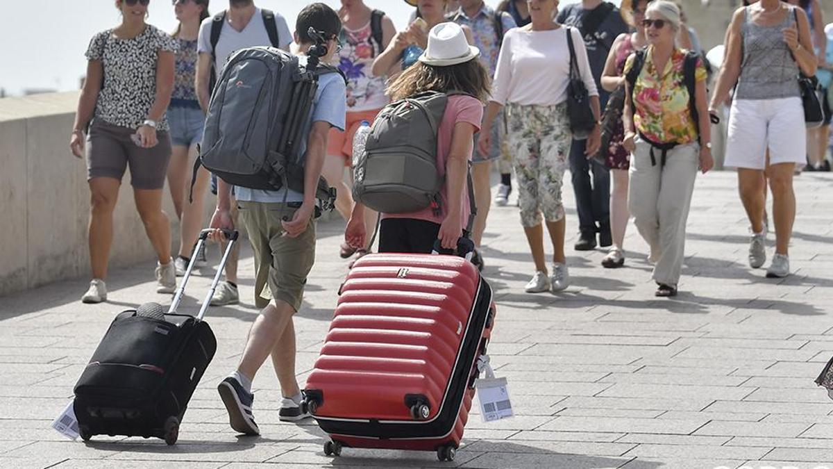 Imagen de archivo de un grupo de jóvenes arrastrando maletas por el Puente Romano