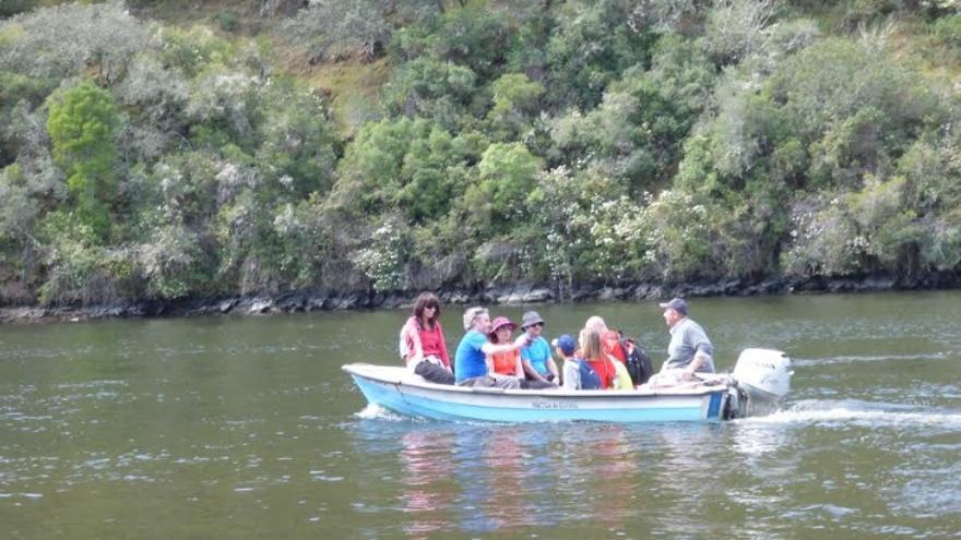 Varias personas cruzan el río Sever, la frontera entre España y Portugal, montadas en el barco 'patera'