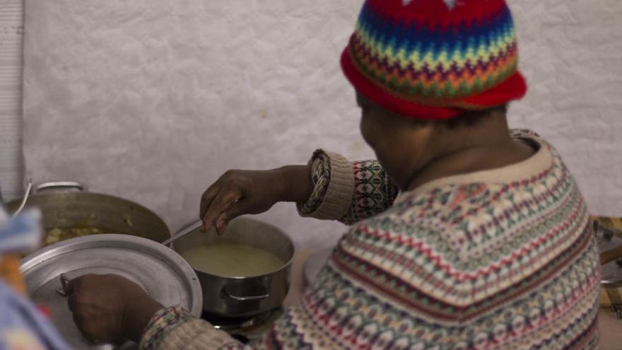 Virginia Montaño cocina un puchero en un local ocupado, que antes servía como uno de los mayores puntos de venta de drogas de Barcelona
