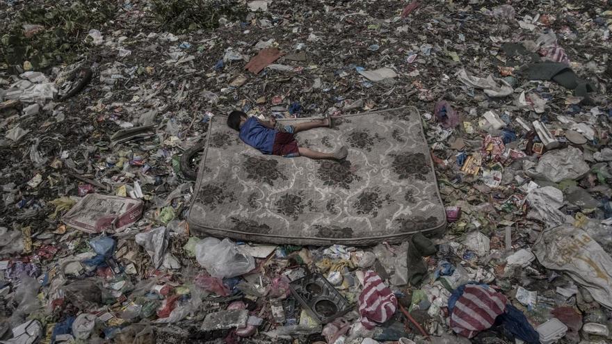 'Living Among What's Left Behind', tercer premio de la categoría 'Medio ambiente'. Un niño que recolecta material reciclable tumbado en un colchón rodeado de basura que flota en el río Pasig, en Manila (Filipinas)