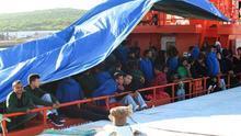 Varios migrantes amanecen tras pasar la noche en la cubiertos del Concepción Arenal bajo una lona de plástico.