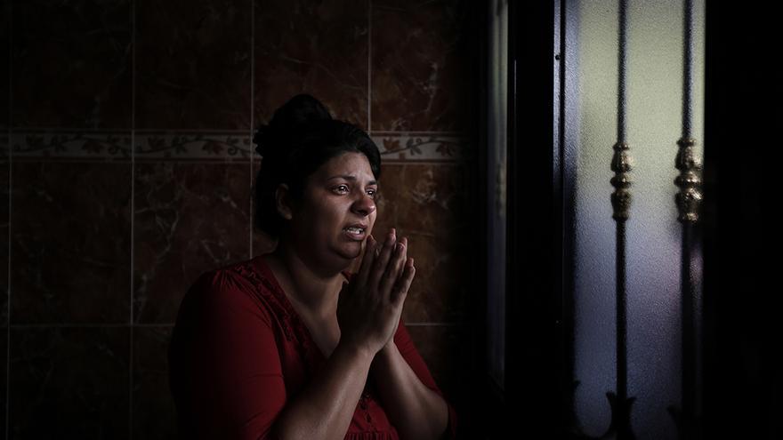 Raquel reza y llora en la entrada de la casa donde vive con su familia (su marido José y sus cinco hijos) durante su desahucio el 19 de mayo.  | OLMO CALVO