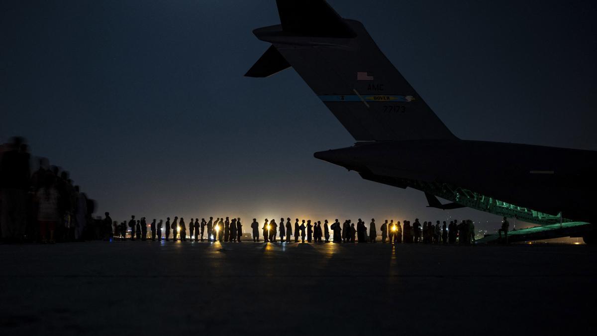 Una tripulación de la Fuerza Aérea de Estados Unidos se prepara para cargar a un grupo de evacuados.