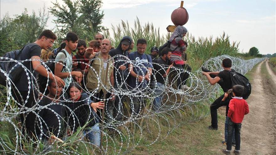Varios refugiados sirios intentan saltar la alambrada de la frontera entre Hungría y Serbia en Röszke, Hungría el pasado martes/ Efe