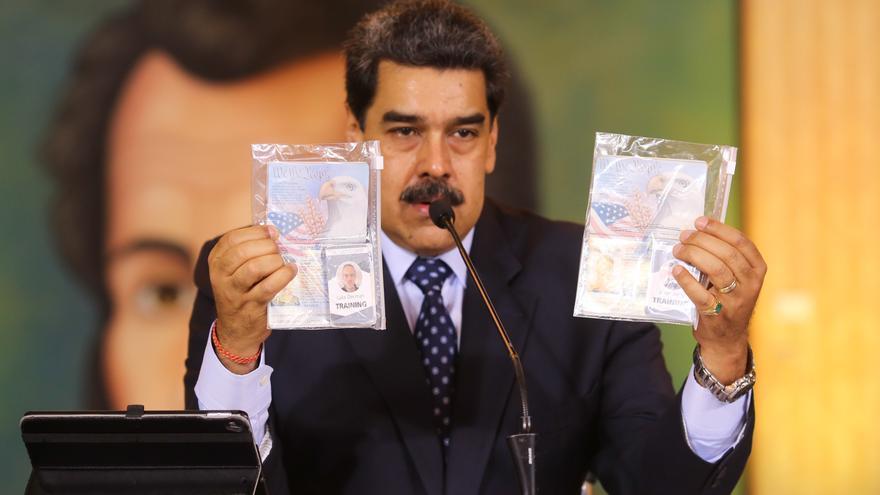 El presidente venezolano, Nicolás Maduro, muestra los pasaportes de dos ciudadanos estadounidenses, acusados por el gobierno venezolano de participar en un supuesto intento de incursión durante una rueda de prensa sobre un presunto golpe de estado.