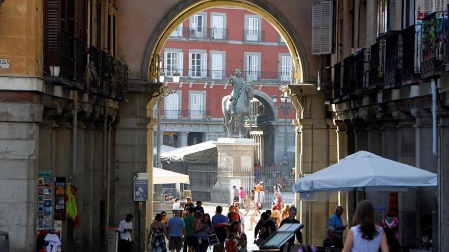 Turistas se dirigen a la plaza Mayor por una de sus entradas típicas.