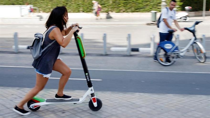Una mujer se sube a un patinete en Madrid.