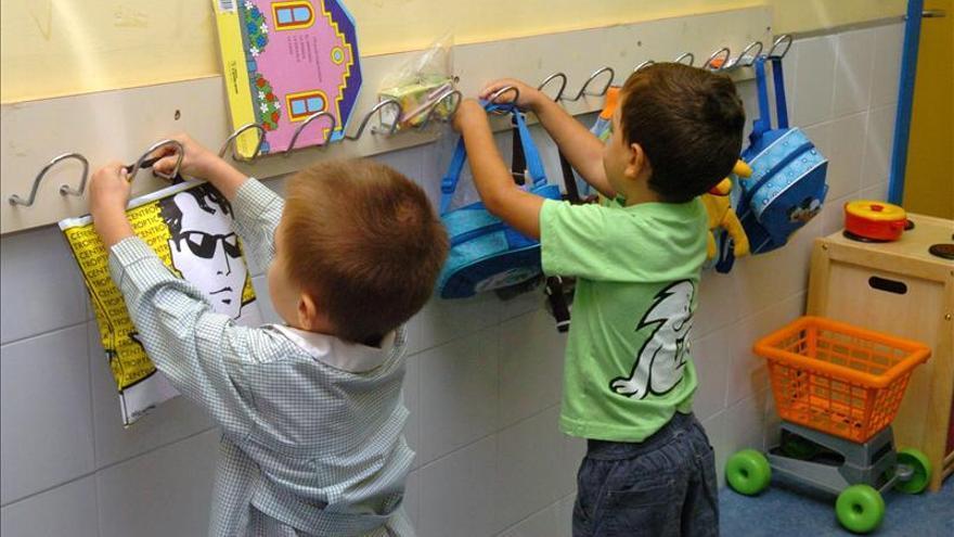 Alumnos de infantil colocando sus mochilas en los colgadores.