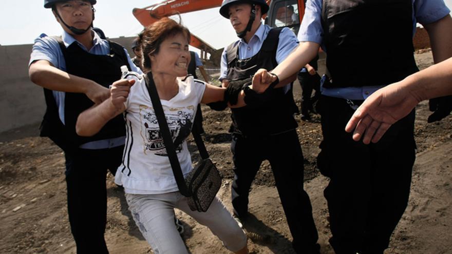 Arresto de una mujer que se opone a los desalojos en el distrito de Changchun noreste de la provincia Jilin, China, el 9 de junio de 2010. Fang Xinwu/Color China Photo/AP Photo