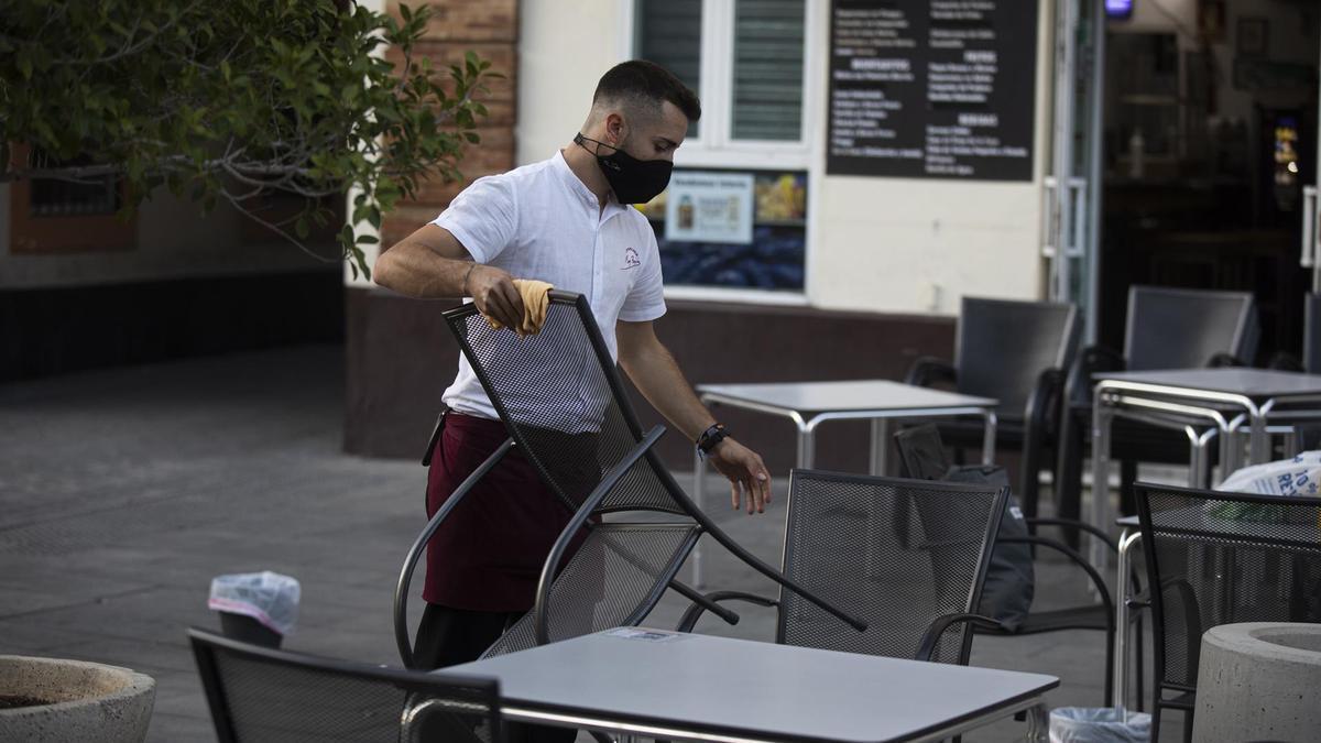 Un camarero recoge la terraza.