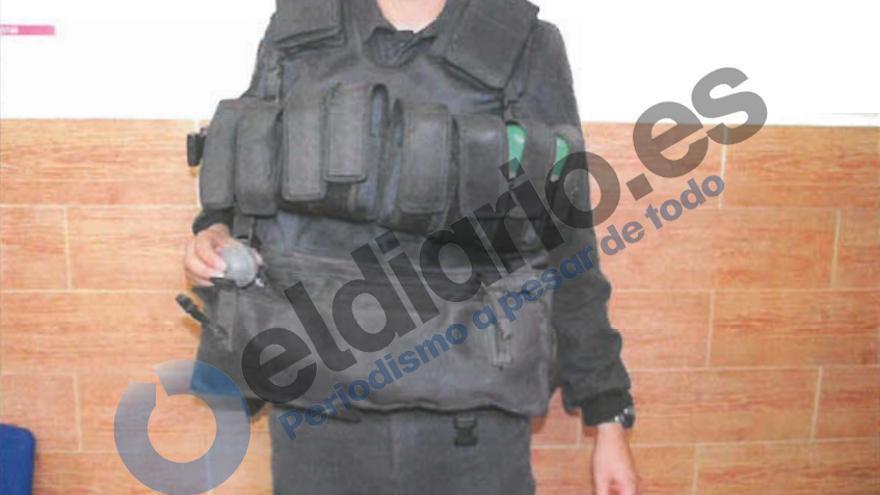 Un agente de la Guardia Civil muestra una pelota de goma como las lanzadas el 6 de febrero en el intento de entrada en el que murieron 15 inmigrantes, ataviado con el chaleco empleado, cargado de botes de humo./ Informe de la Policía Judicial de la Guardia Civil sobre la tragedia de Ceuta