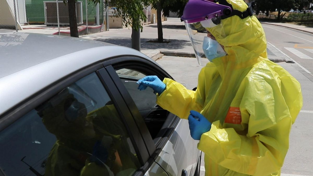 Un sanitario realiza una prueba PCR en la calle.