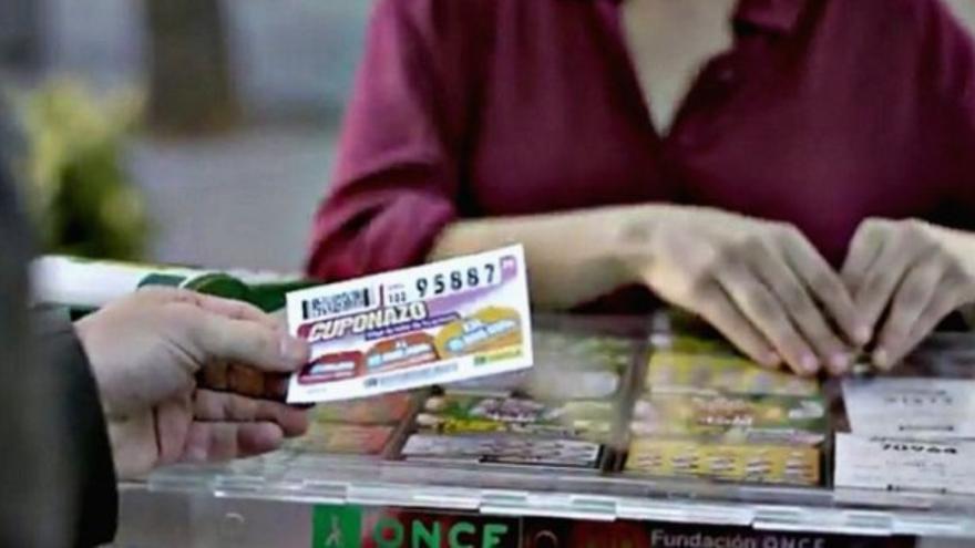 Un vendedor de la ONCE entrega un cupón a un cliente