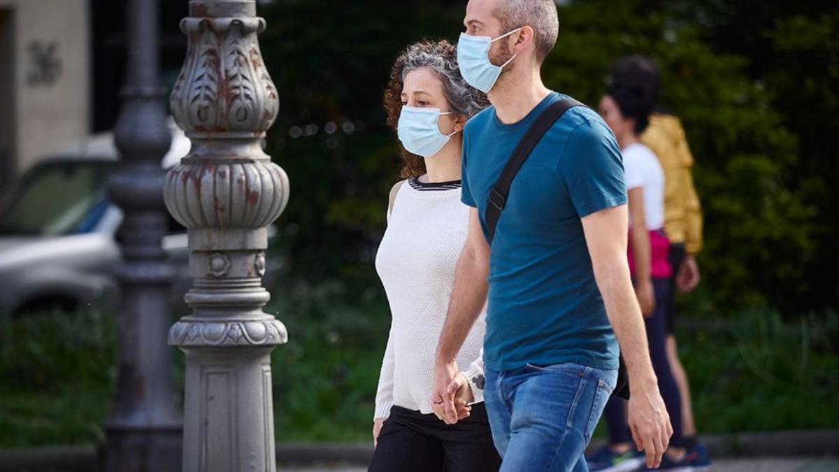Imagen de archivo de dos personas caminando con mascarilla en una calle