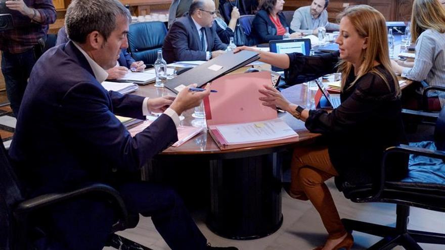 El presidente del ejecutivo regional, Fernado Clavijo y la consejera de Hacienda, Rosa Dávila, intercambian unos portafirmas, momentos antes de iniciarse la reunión del Consejo de Gobierno. EFE/Ángel Medina G.