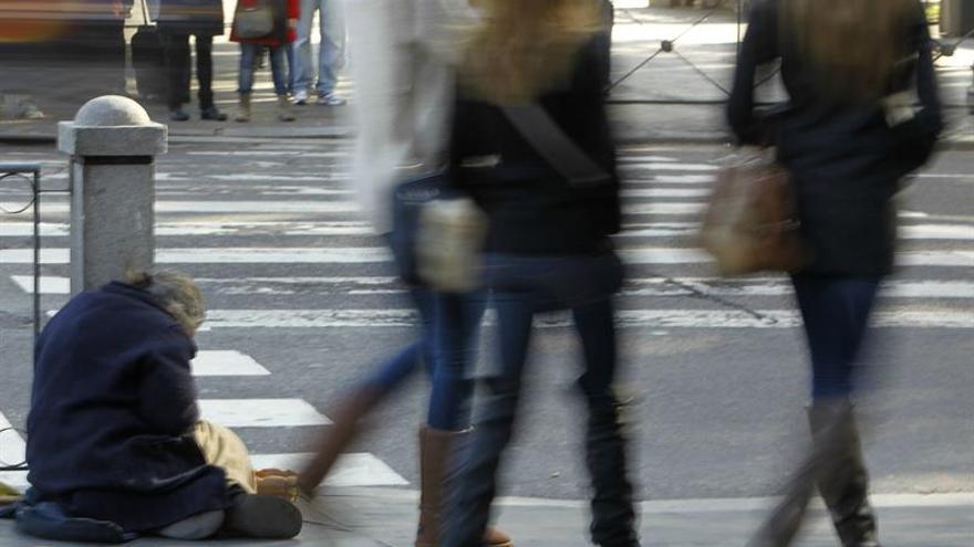 Una persona pide limosna en la Plaza de Cibeles de Madrid