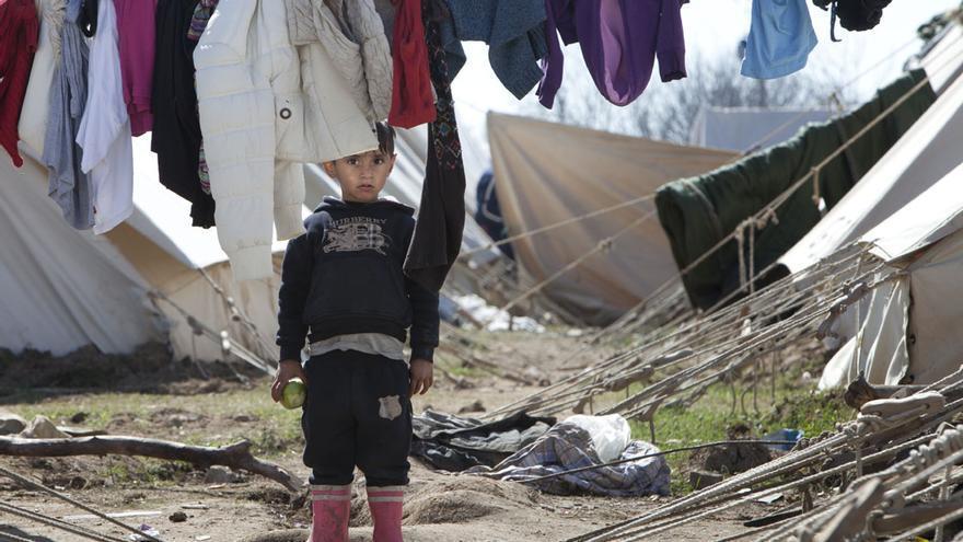 Un niño en el campo de refugiados de Idomeni mira a la cámara mientras sujeta una manzana.   Eduardo Rivas