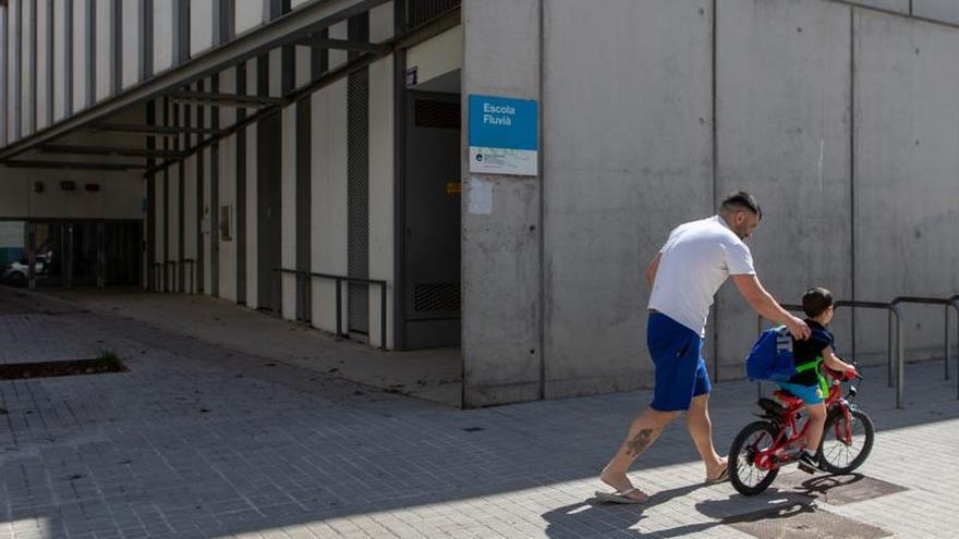 Un padre y su hijo pasean frente a una escuela cerrada en el barrio del Poble Nou de Barcelona