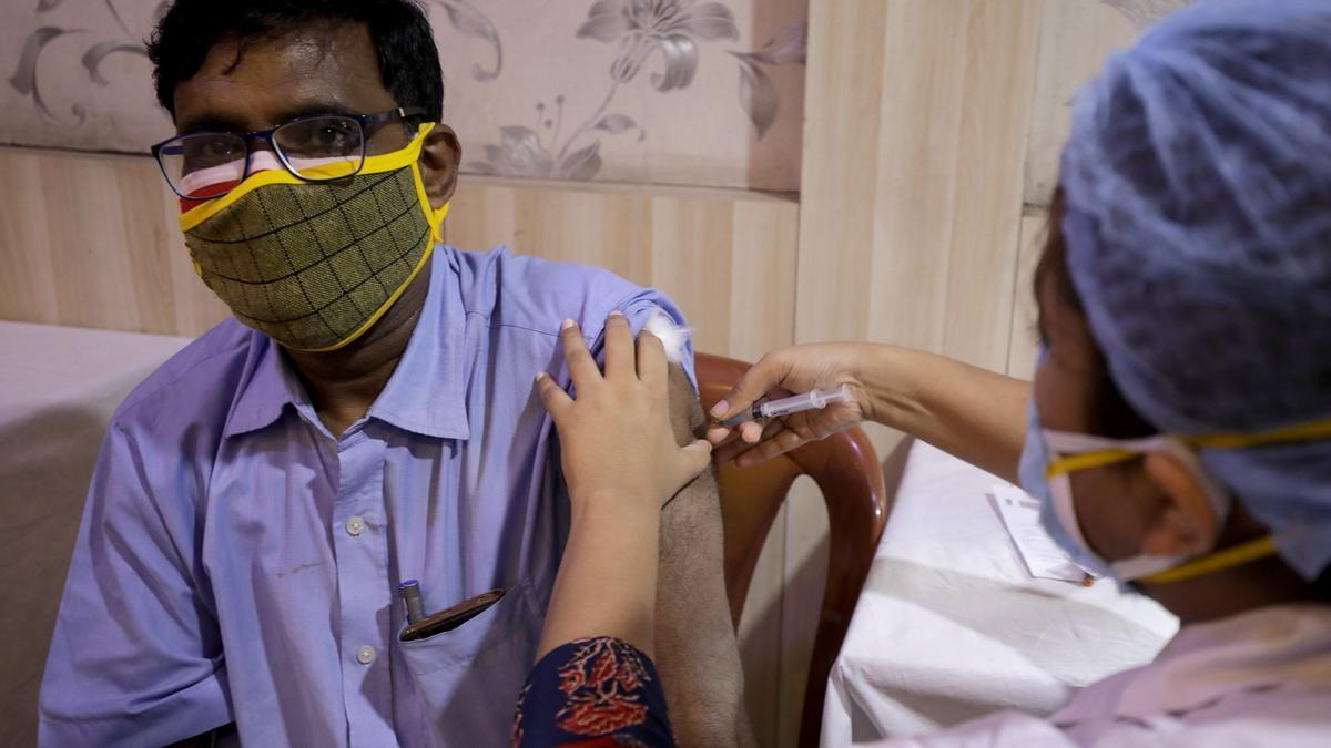 Un hombre indio recibe una vacuna COVID-19, dentro de un centro de vacunación en el Press Club en Calcuta, India Oriental.