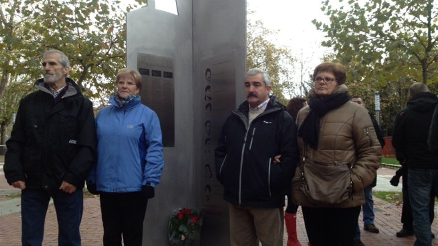 Familiares de víctimas del 3 de Marzo junto a la escultura de homenaje.