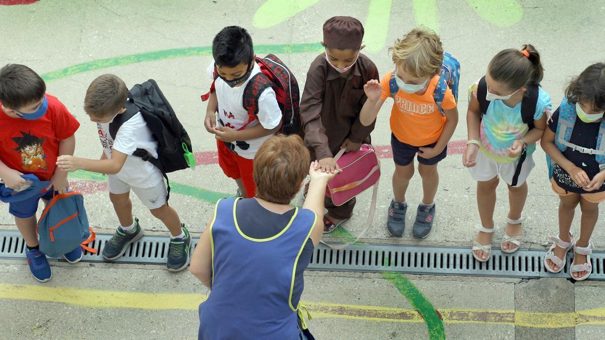 Varios niños y niñas saludan a su maestra en el primer día de clase en un colegio.