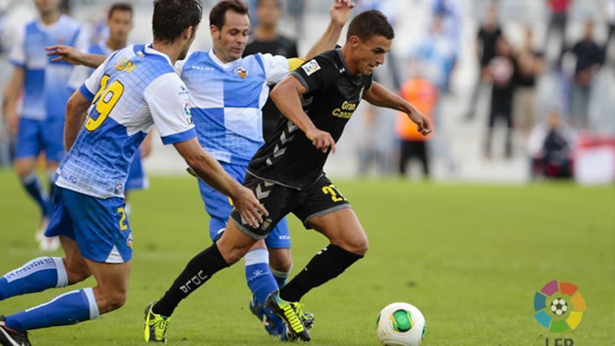 El canterano de la UD Las Palmas Asdrúbal conduce el balón ante la mirada de jugadores del Sabadell. LFP