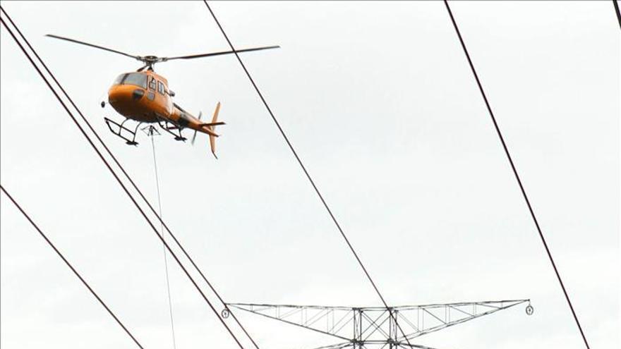 Un helicóptero tiende un cable de alta tensión para evitar la tala de árboles