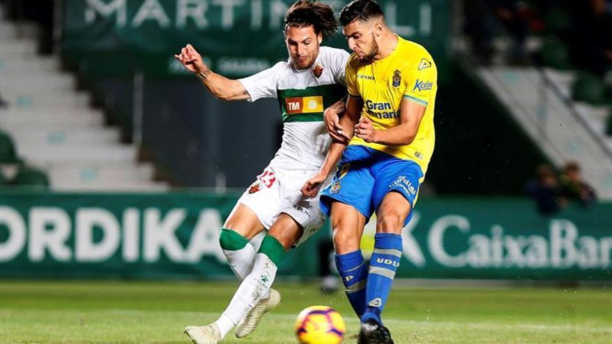 El delantero de la UD Las Palmas, Rafa Mir (d), intenta golpear el balón ante el defensa del Elche, Juan Cruz. EFE / Manuel Lorenzo.