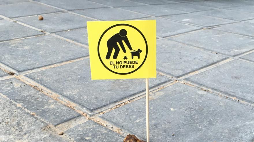 Un excremento de perro con la bandera elaborada por la Asociación de Vecinos
