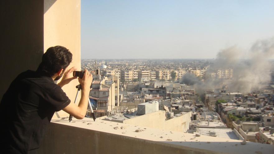 Un activista hace fotos del humo procedente de Juret al-Shayah, en Homs, julio 2012 © REUTERS/Shaam News Network/Handout