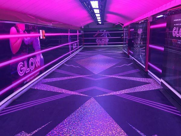 Pasillo de la estación de Chueca con los neones rosas de la nueva campaña promocional de la serie GLOW | Fotografía: Somos Chueca
