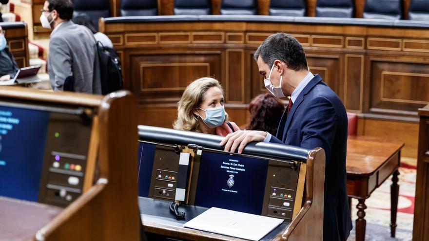 El presidente del Gobierno, Pedro Sánchez (i) y la ministra de Economía y vicepresidenta tercera del Gobierno, Nadia Calviño (d), conversan en el Parlamento
