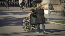 Una mujer empuja a otra en una silla de ruedas.