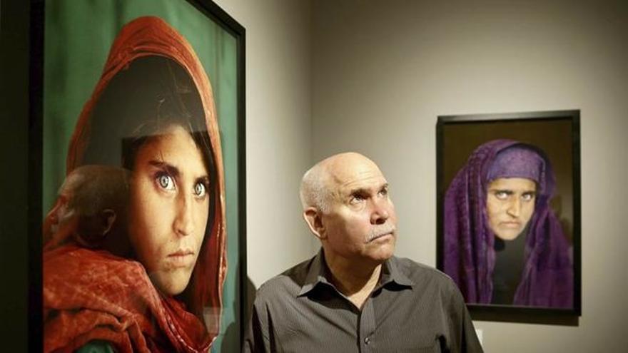 Steve McCurry entre sus dos fotografías de Sharbat Gula