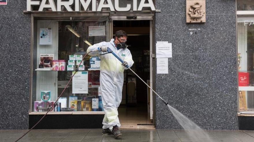Un trabajador municipal desinfecta los alrededores de una Farmacia.