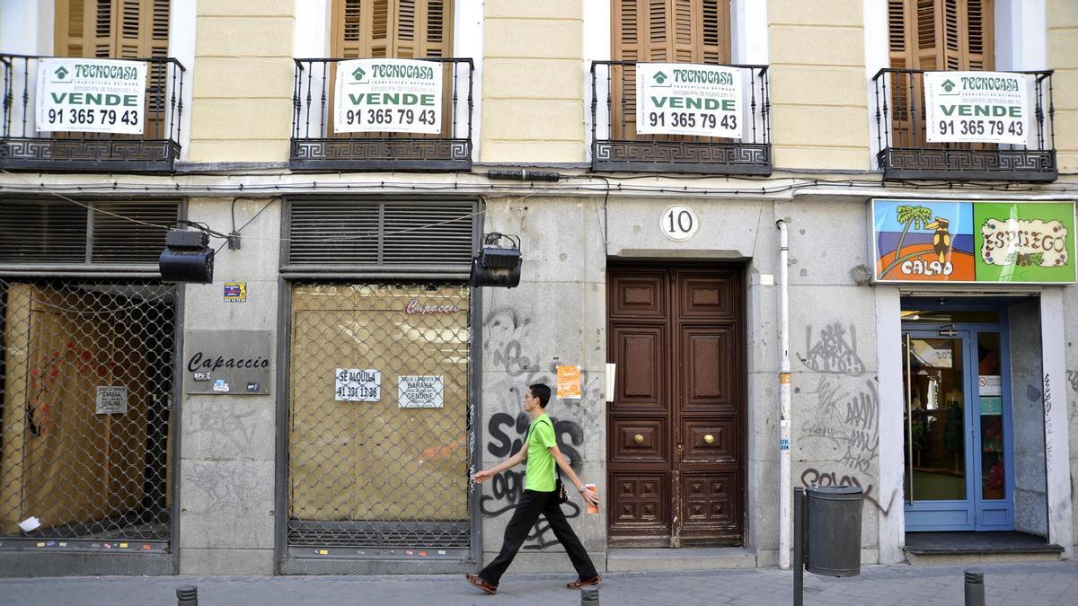 """Vista parcial de la fachada de un edificio de viviendas ubicado en la calle del Duque de Alba con varios carteles de """"Se vende""""."""