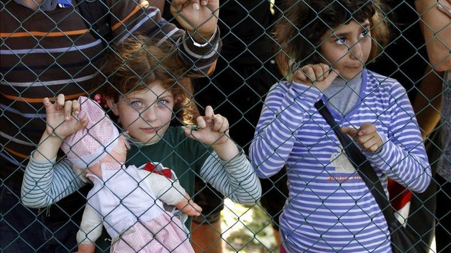 Dos niños refugiados esperan este jueves para registrarse tras haber cruzado la frontera entre Serbia y Croacia. / Efe.