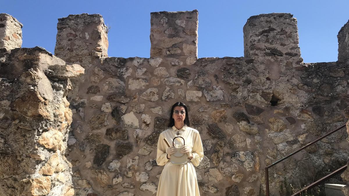 Miss Beige agarra su bolso delante de la muralla del pueblo madrileño de Buitrago