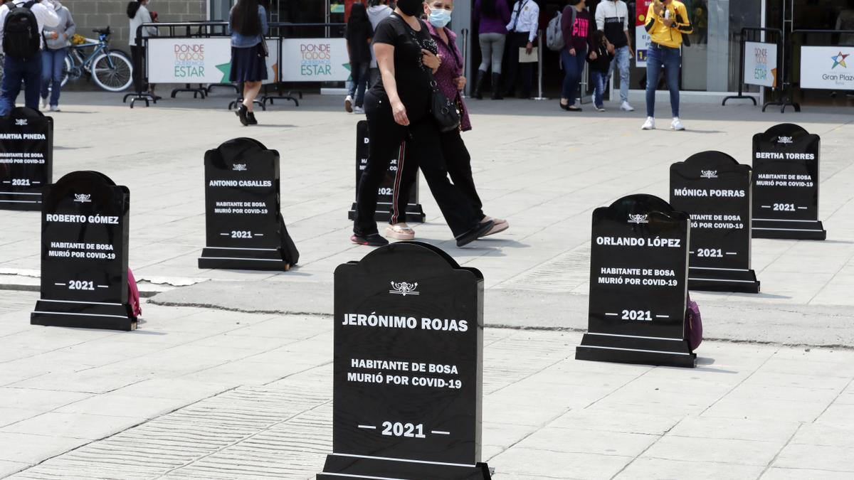 Habitantes de la localidad de Bosa observan hoy lápidas con nombres de algunas de las personas fallecidas por la COVID-19, en el sur de Bogotá (Colombia).