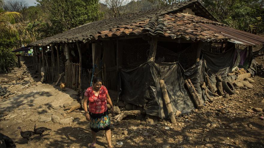 Blanca, madre de Víctor, camina frente a su casa en busca de leña para preparar la comida