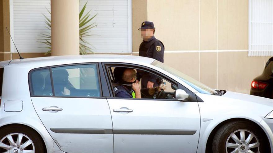 La joven de 19 años, de origen marroquí, detenida hoy en Fuerteventura por supuestamente pertenecer a la estructura de la organización terrorista Dáesh, sale custodiada de la comisaría de Puerto del Rosario.