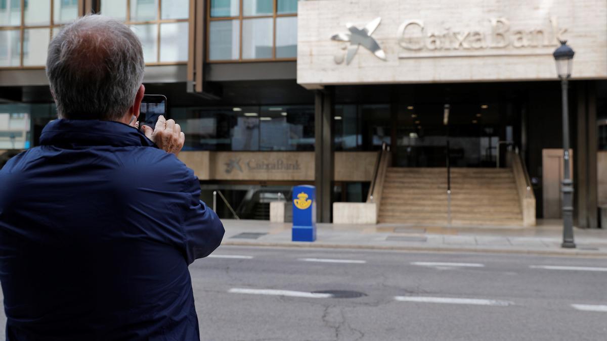 Un hombre toma una foto del logo de Caixabank. EFE/Manuel Bruque/Archivo