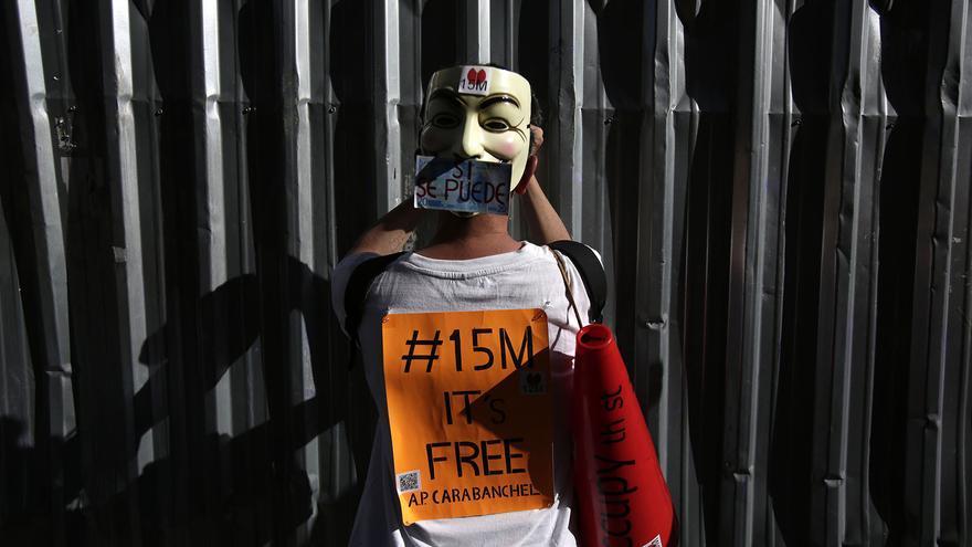 Un manifestante coloca un cartel durante la manifestación del 12M. / Fotografía: Olmo Calvo.