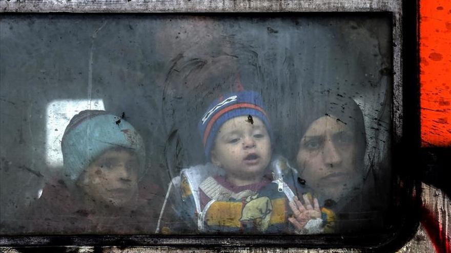 Un familia de refugiados mira a través de la ventana del tren antes de partir hacia a la frontera serbia. | Efe