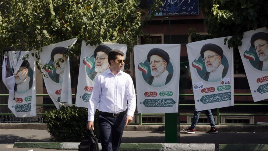Un hombre pasa por delante de los carteles del candidato presidencial Ebrahim Raisi en una calle de Teherán.