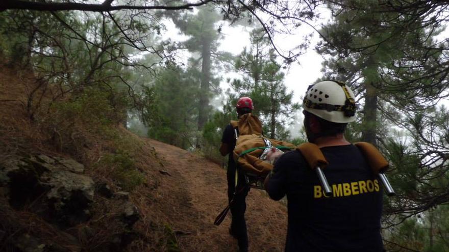 En la imagen, dos bomberos portan en camilla a una senderista francesa en la Ruta de los Volcanes. Foto. BOMBEROS LA PALMA.