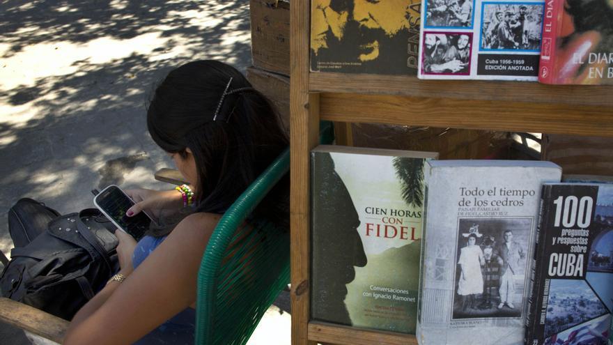 Una vendedora callejera de libros usando el móvil en La Habana / AP Photo/Ramón Espinosa