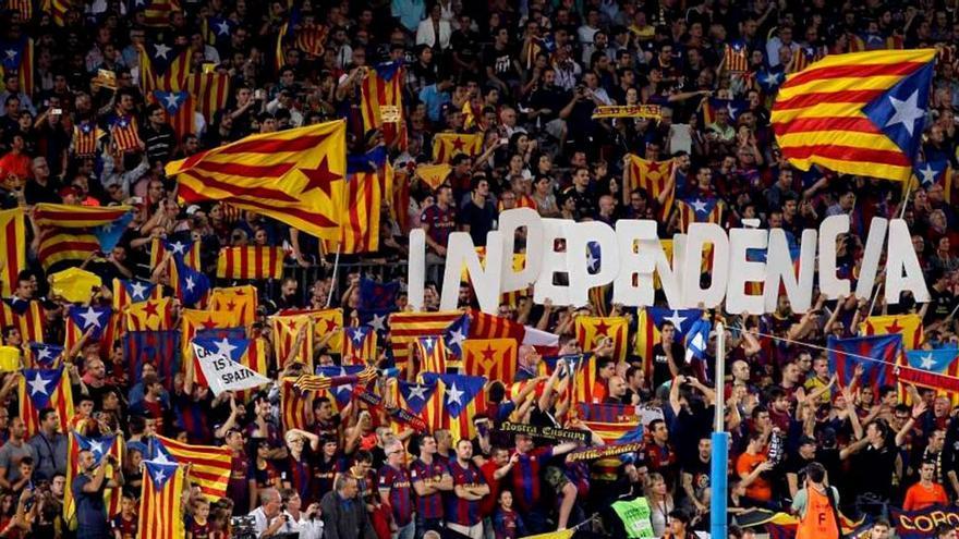 Independentistas catalanes izan banderas durante el último clásico. (EFE)